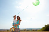 Mother and daughter carrying balloon