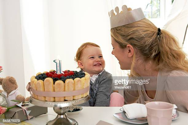 Mother and daughter celebrating little girls first birthday with self-made fancy cake