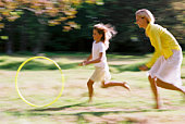Mother and daughter chasing hoop