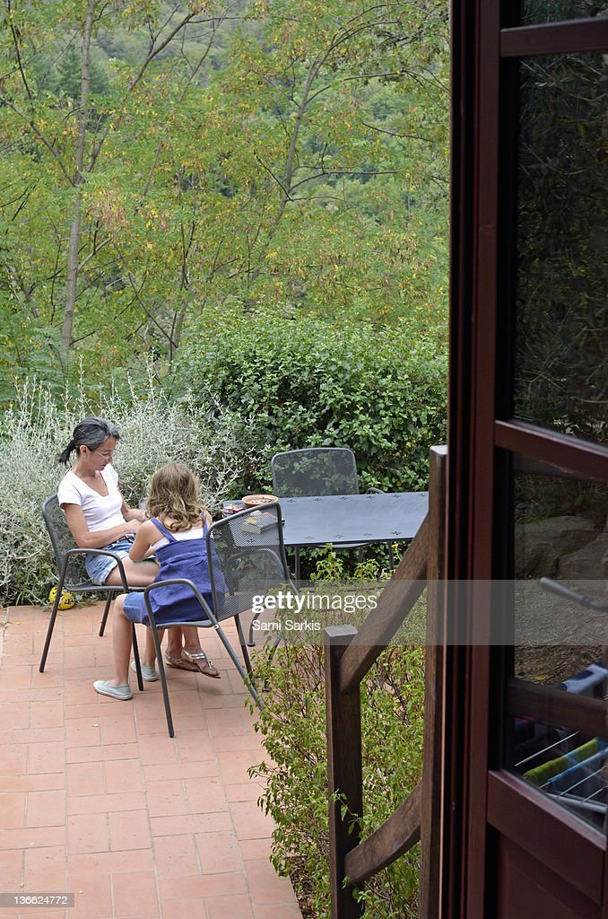 Mother and daughter chating in garden : Stock Photo