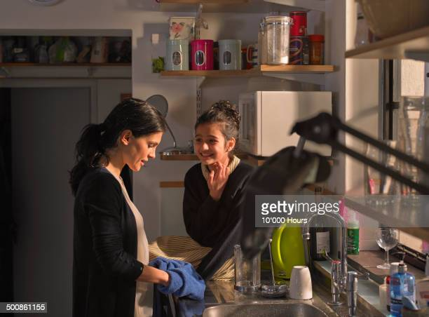 Mother and daughter chatting whilst mum washes up