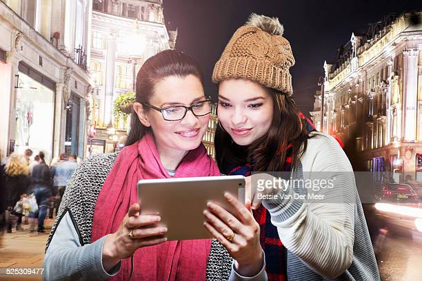 mother and daughter check digital tablet in city.