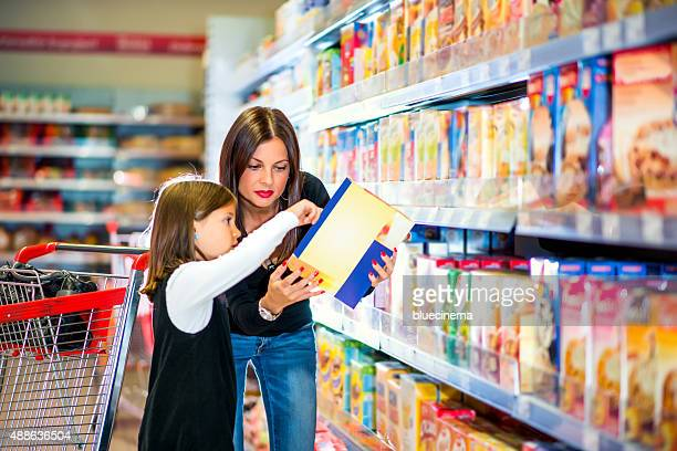 Madre e hija comprobación de la etiqueta de alimentos en el supermercado