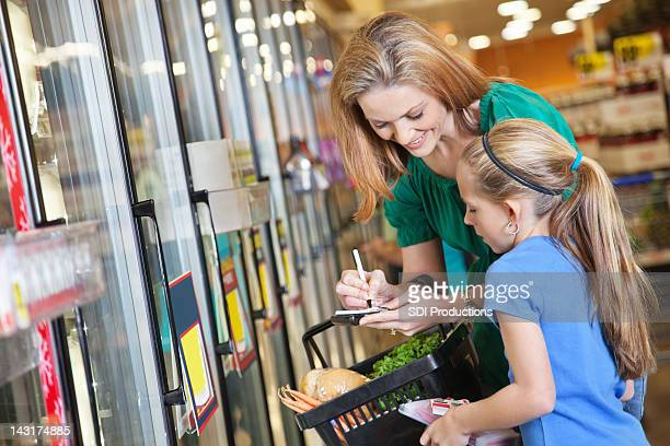 Mother and daughter checking shopping list at the grocery store