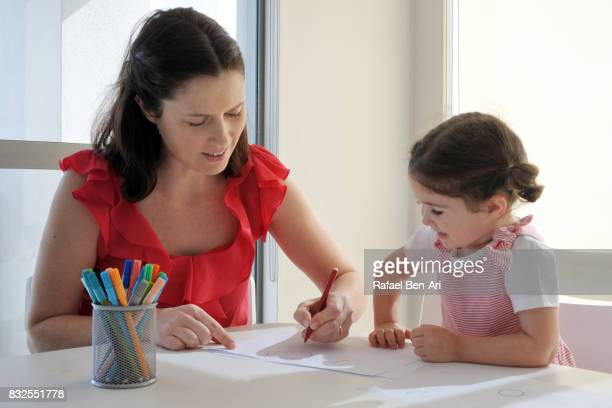 Mother and daughter child draw and paint together