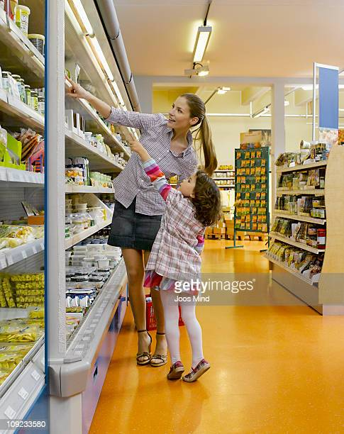 mother and daughter choosing diary produce