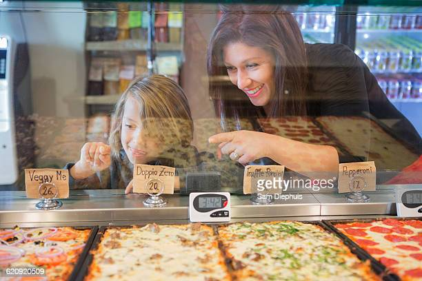 Mother and daughter choosing pizza in cafe