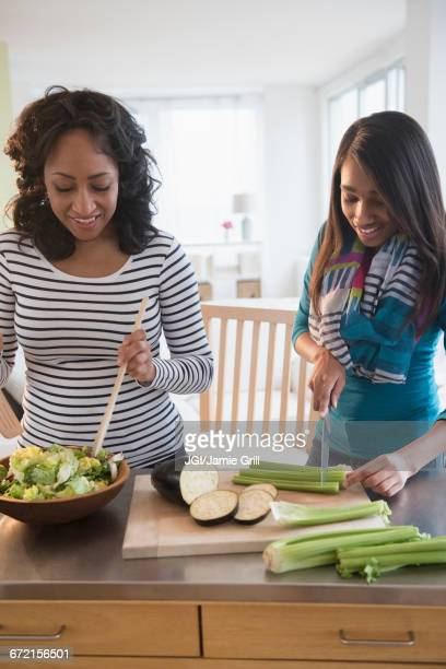 Mother and daughter chopping vegetables for salad