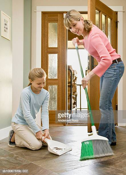 Mother and daughter (10-11) cleaning floor next to doorway, smiling