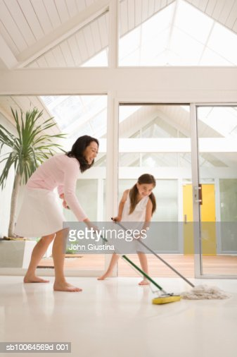 Mother and daughter (6-7) cleaning floor, smiling : Stock Photo