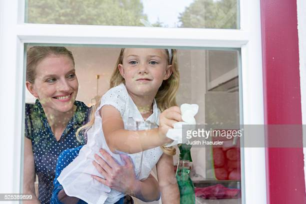 Mother and daughter cleaning window