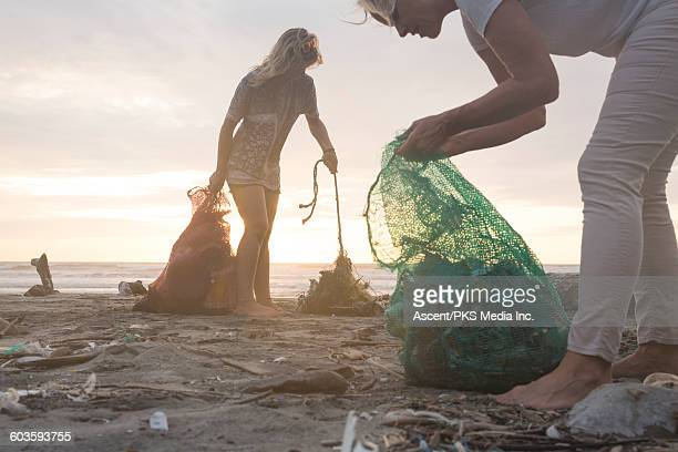 Mother and daughter collect garbage from beach