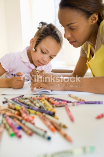 Mother And Daughter Coloring With Crayons Stock Photo