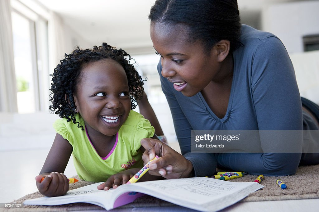 Mother and daughter colouring in lying on rug : Stock Photo