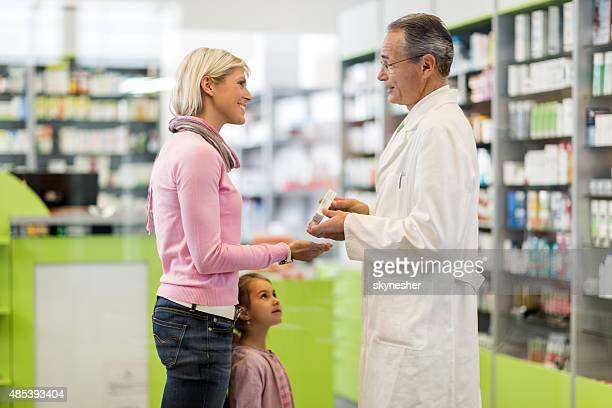 Mutter und Tochter, die Kommunikation mit Apotheker in Apotheke.