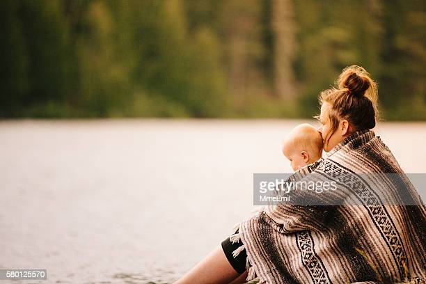 Mother And Daughter Contemplating A Calm Lake