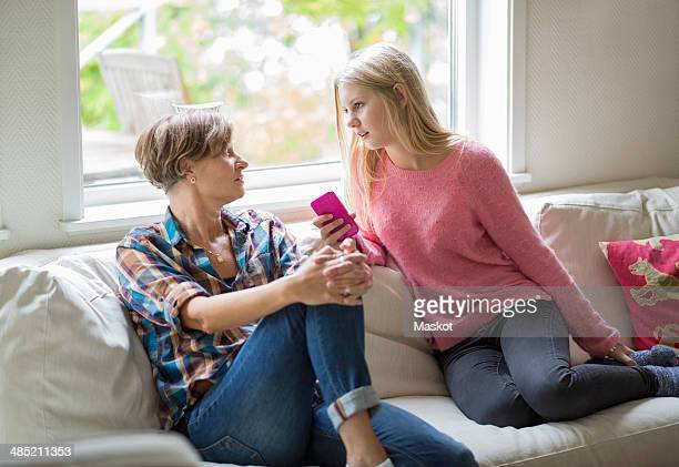 Mother and daughter conversing in living room
