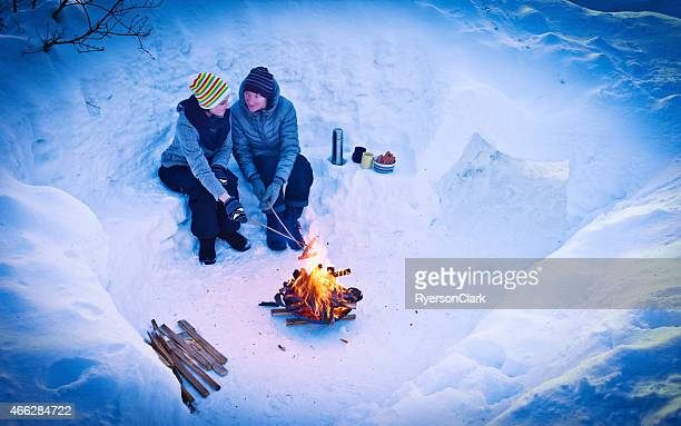 Mother and Daughter Cook Hot Dogs Over a Fire Pit.