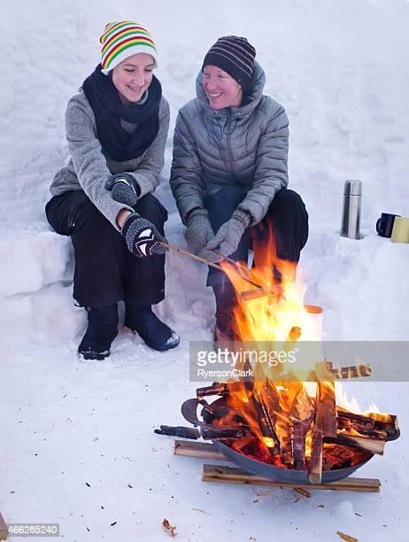 Mutter und Tochter Kochen Hot Dogs über eine Feuerstelle.