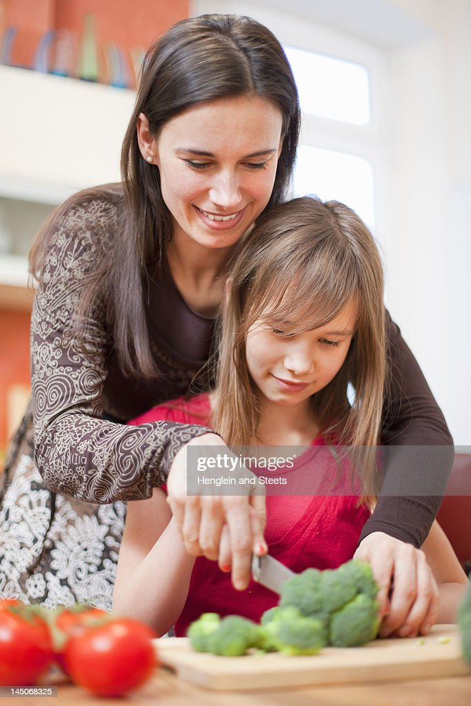 Mother and daughter cooking together : Stock Photo