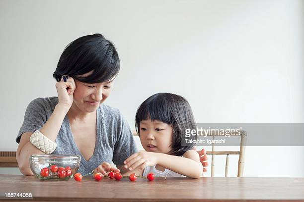 Mother and daughter counting cherries