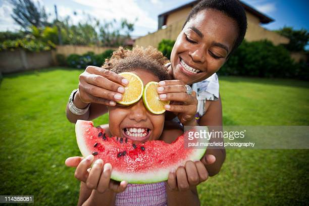 Mother and daughter creating fruit face