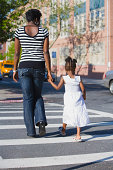 Mother and daughter crossing street