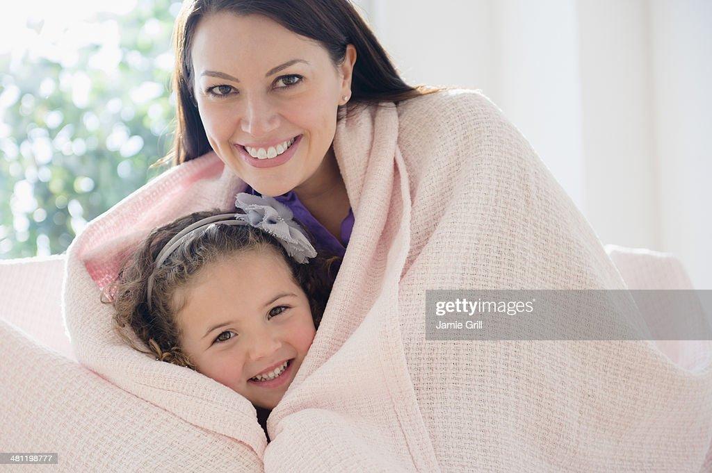 Mother and daughter cuddling under blanket