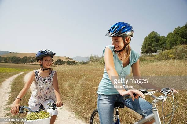 Mother and daughter (9-11) cycling, smiling at each other