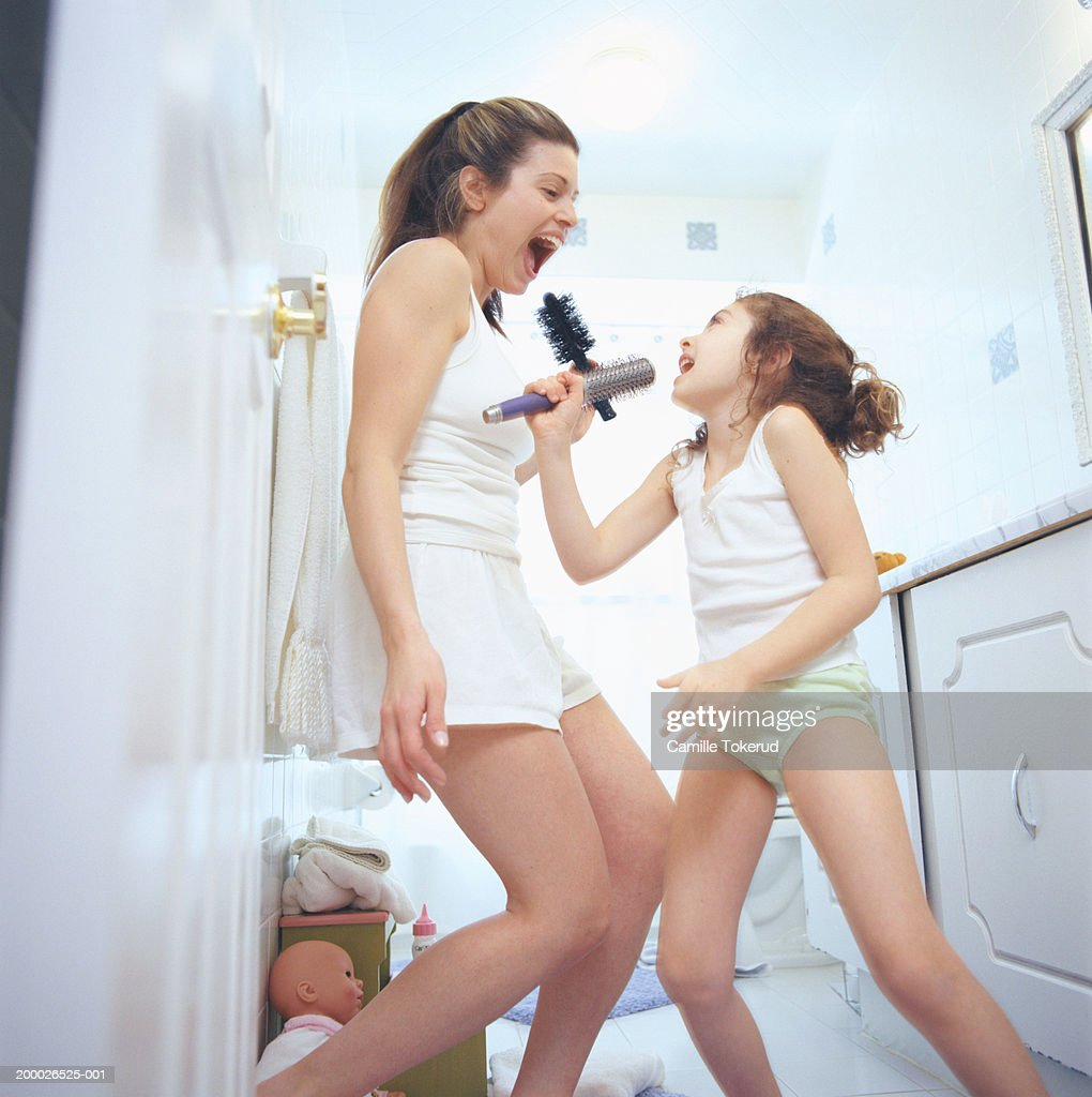 Mother and daughter (4-6) dancing and singing in bathroom