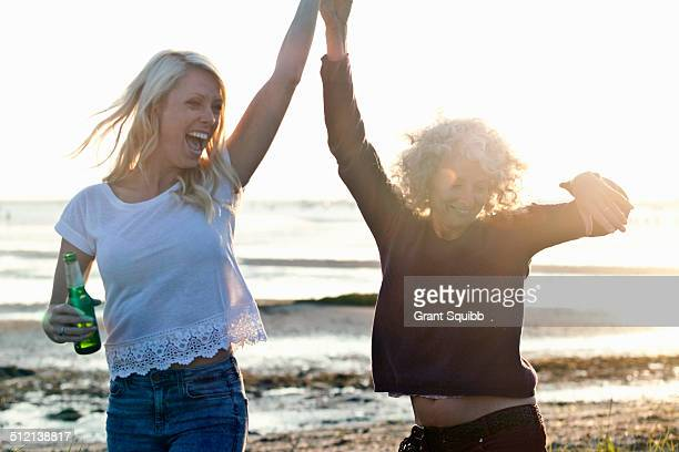 Mother and daughter dancing on Bournemouth beach, Dorset, UK