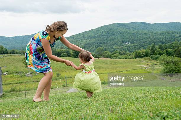 Mother and daughter dancing together in field