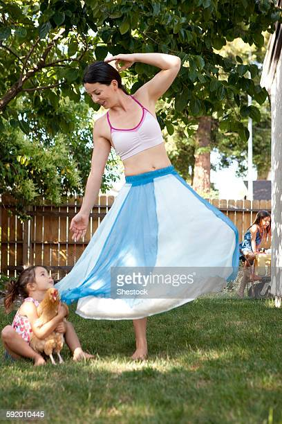 Mother and daughter dancing with chicken in backyard