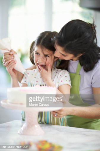 Mother and daughter (4-5) decorating cake : Stock Photo