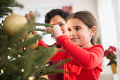 Mother and daughter decorating Christmas tree