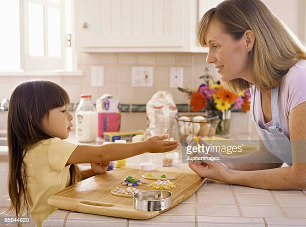 Mother and daughter decorating cookies