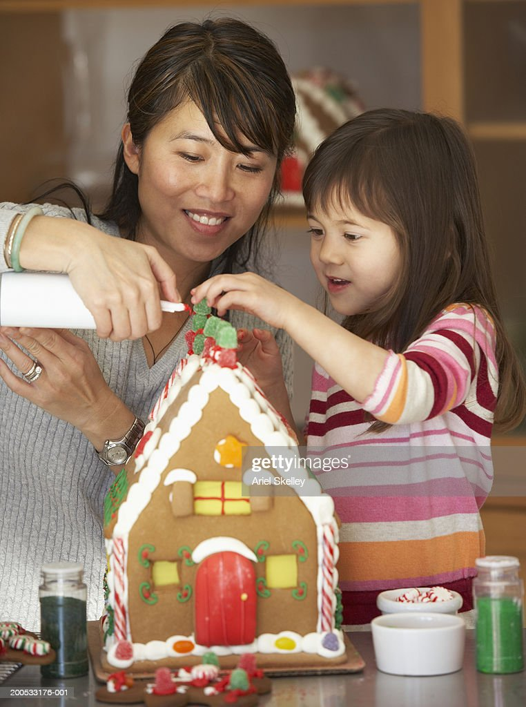 Mother and daughter (4-5) decorating gingerbread house, smiling : Stock Photo