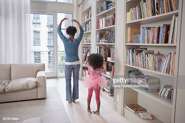 Mother and daughter doing ballet in the living room