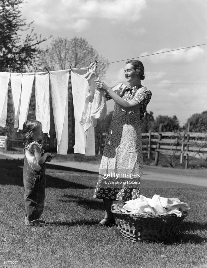 Mother And Daughter Doing Laundry Hanging Wash On Clothesline In Backyard Clean Laundry In Wicker Basket Mother Smiling Wearing Apron. : Stock Photo