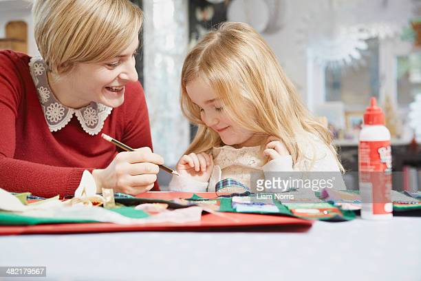 Mother and daughter drawing at kitchen table