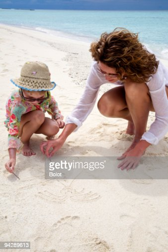Mother and daughter drawing on sand : Stock Photo