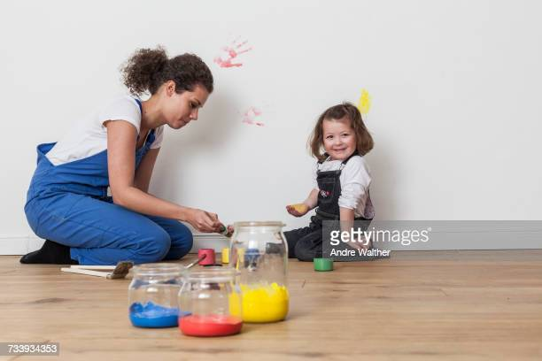 Mother and daughter drawing on white wall