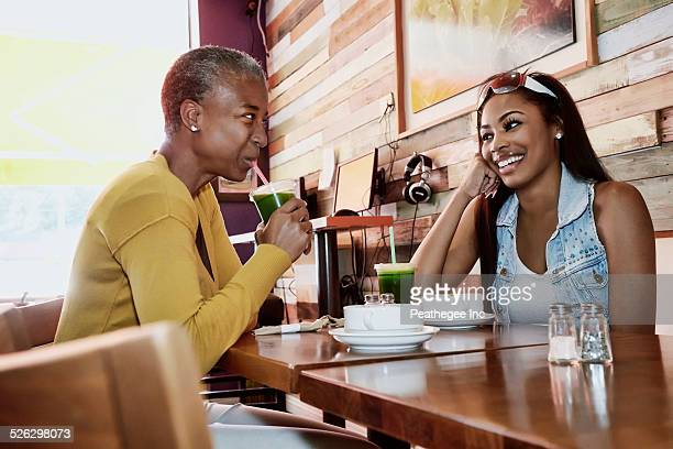 Mother and daughter drinking juice in cafe