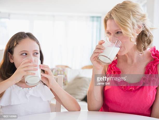 Mother and daughter (8-9 years) drinking milk