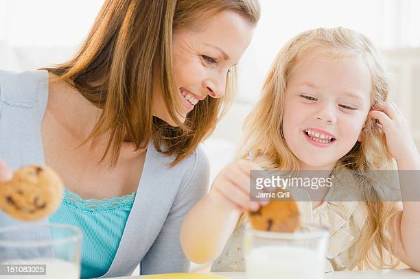 Mother and daughter dunking cookies in milk