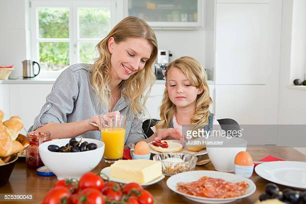 Mother and daughter eating at kitchen table