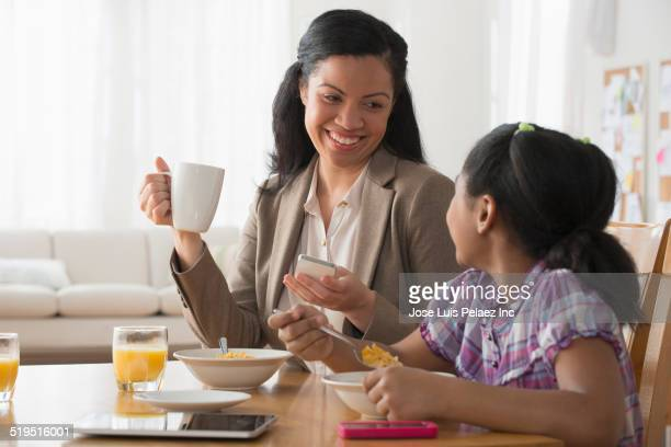 Mother and daughter eating breakfast together
