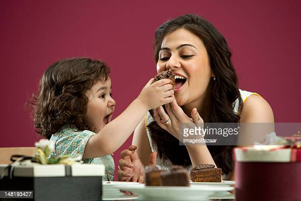 Mother and daughter (2-3) eating cake