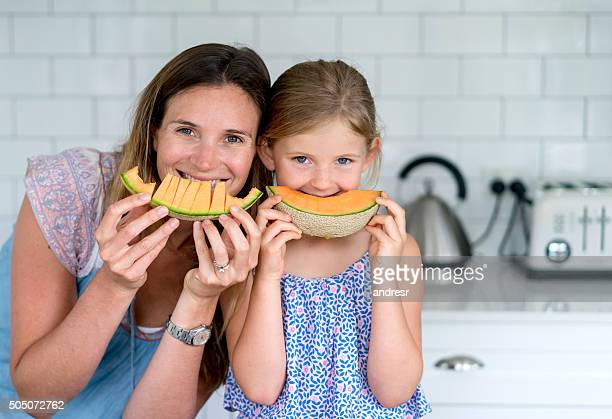 Mother and daughter eating melon