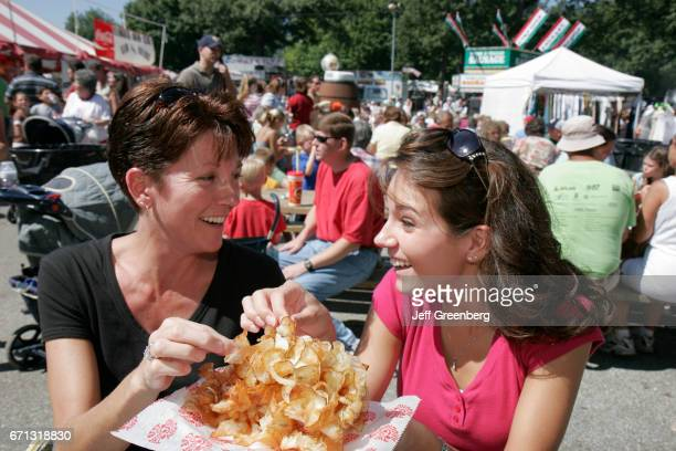 A mother and daughter eating potato chips at Marshall County Blueberry Festival